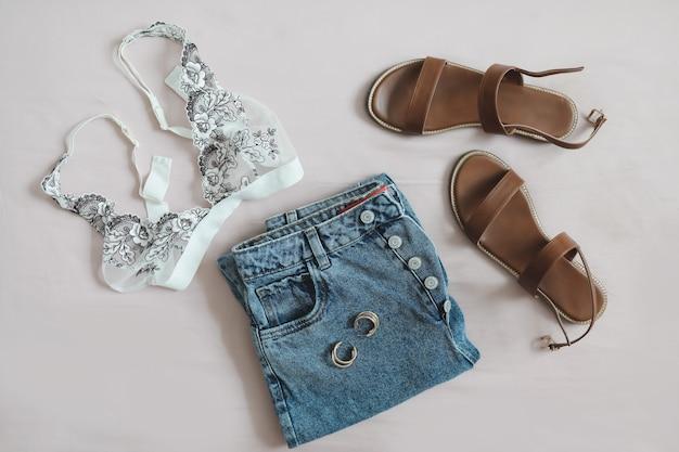 Плоская композиция с джинсовыми шортами и сандалиями женского нижнего белья на бежевом фоне, вид сверху