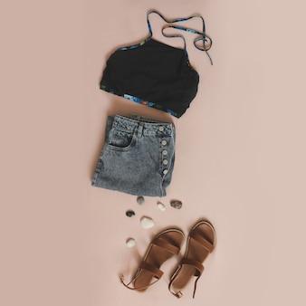 Плоская композиция с женскими купальниками, джинсовыми шортами и сандалиями на бежевом фоне, вид сверху