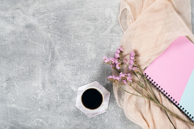 Flat lay composition with feminine scarf, coffee cup, pink dry flowers, paper notebook on concrete surface.