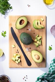 Плоская композиция со свежими авокадо на деревянной основе. вертикальный формат.