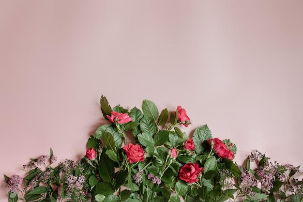 Плоская композиция со свежими цветами на розовом фоне.