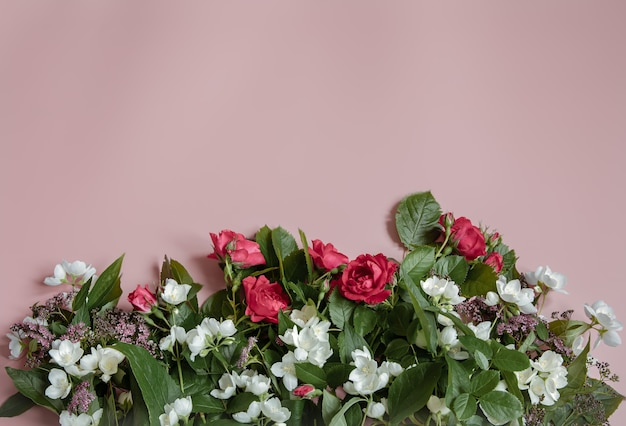 ピンクの表面に生花を使ったフラットレイコンポジション