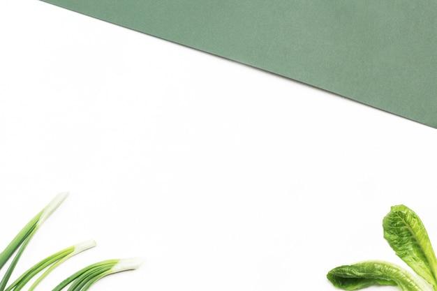 Плоская композиция со свежей зеленью на бело-зеленом фоне