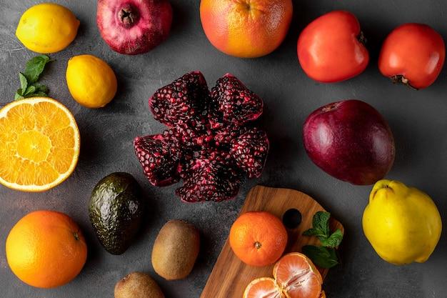 신선한 여러 가지 빛깔의 과일이 있는 평평한 구성. 오렌지, 키위, 자몽, 석류, 아보카도, 귤, 감, 어두운 배경에 망고