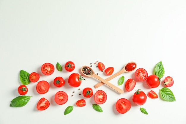 フレッシュトマト、コショウ、バジル、木製のスプーンのテキスト用のスペースとフラットレイアウト構成。熟した野菜