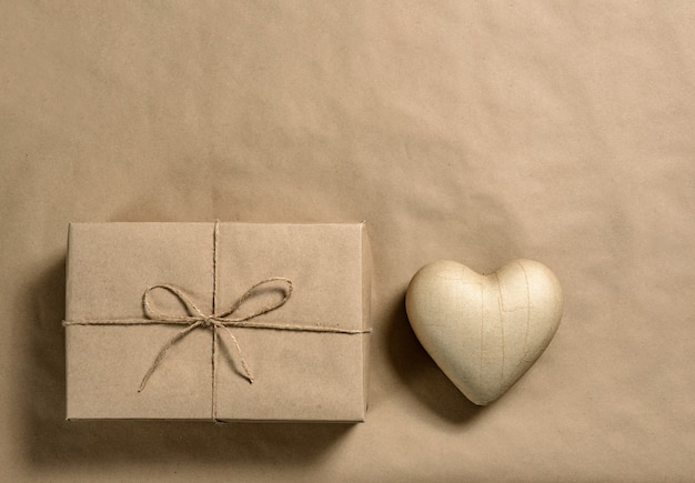 Flat lay composition with a gift box and a heart on a craft paper with copy space