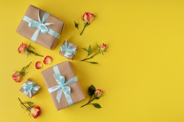 Плоская композиция с подарочными коробками и розами на желтом фоне. женский день или валентина
