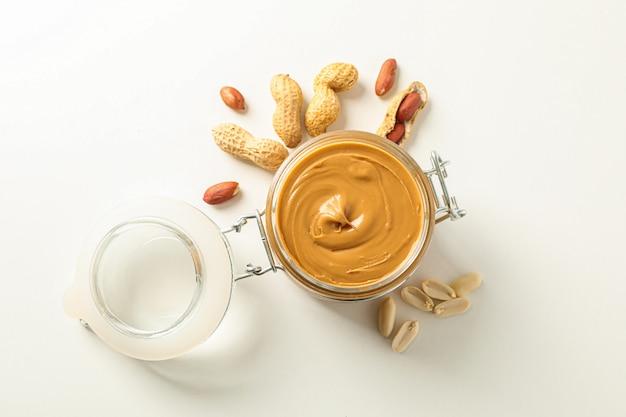 Плоская композиция с стеклянной банкой с арахисовым маслом и арахисом, место для текста и вид сверху