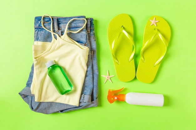 Flat lay composition with green beach accessories on green color.