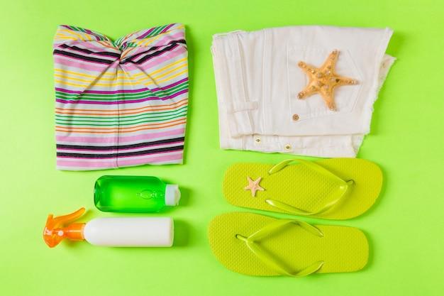 緑の色の背景に緑のビーチアクセサリーとフラットレイ構成。夏休みの背景。休暇や旅行のアイテムの上面図。