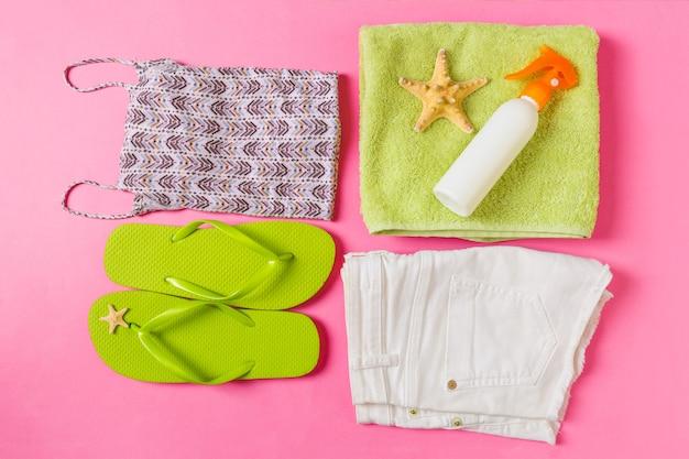ピンクまたは珊瑚色の背景に緑のビーチアクセサリーとフラットレイ構成。夏休みの背景。休暇や旅行のアイテムの上面図