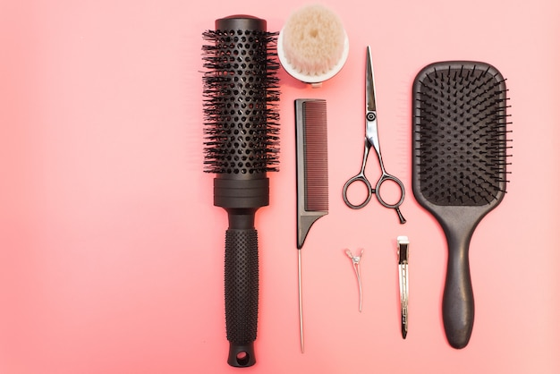 Flat lay composition with hairdresser set on pink surface. barber set with tools and equipment: scissors, combs and hairclips with copy space for text in left. hairdresser and beauty salon service