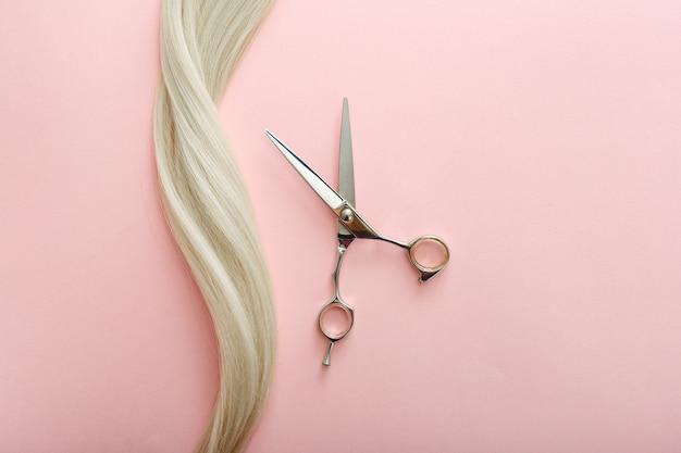 미용사 도구-가 위 및 텍스트 복사 공간 핑크 색상 배경에 금발 머리의 가닥 플랫 누워 구성. 미용사 서비스. 미용실 서비스.