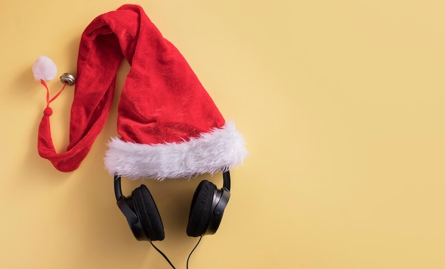 Flat lay composition with headphones and santa claus hat on yellow