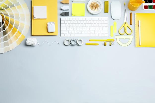明るい背景、テキスト用のスペースにキーボードと文房具を備えたフラットレイコンポジション。デザイナーの職場