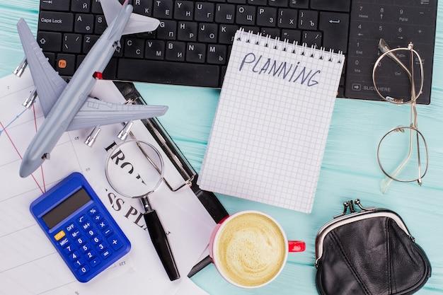 파란색 배경에 키보드, 커피 및 기타 사무실 관련 개체가 있는 평평한 구성. 메모장에 계획 단어입니다.