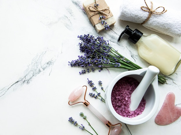 Flat lay composition with lavender flowers and natural cosmetic on marble background