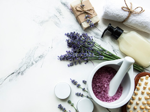 Flat lay composition with lavender flowers and natural cosmetic on marble surface