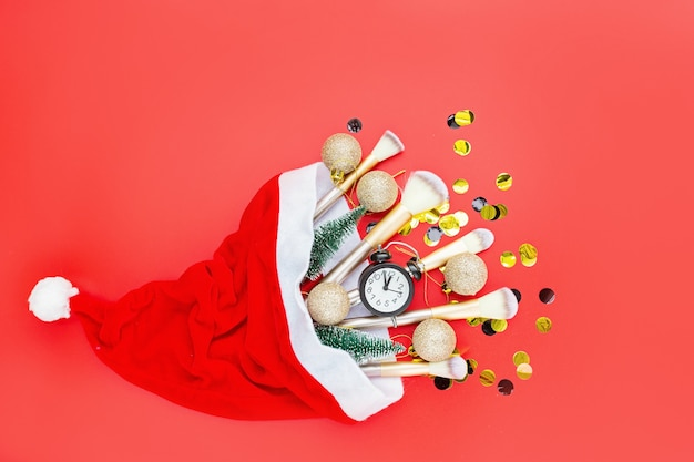 Flat lay composition with makeup brushes and christmas decor on red paper background.