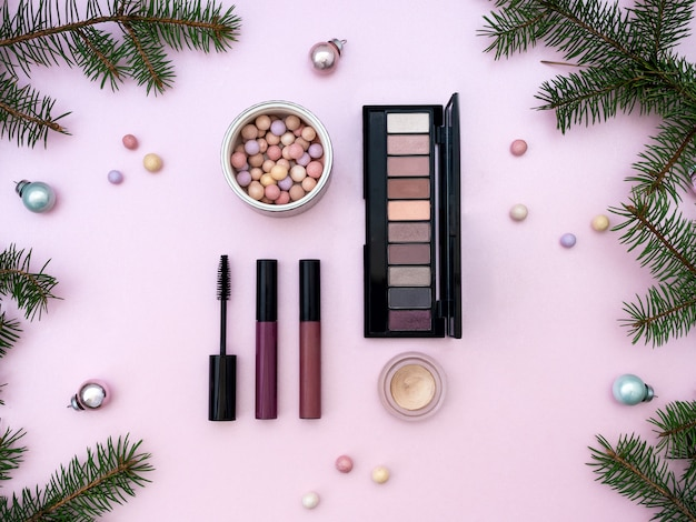 Flat lay composition with makeup cosmetic products and christmas decor on pink background. top view