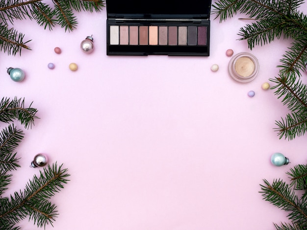 Flat lay composition with makeup cosmetic products and christmas decor on pink background