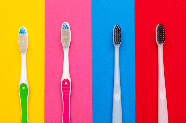 Flat lay composition with manual toothbrushes on color, close up