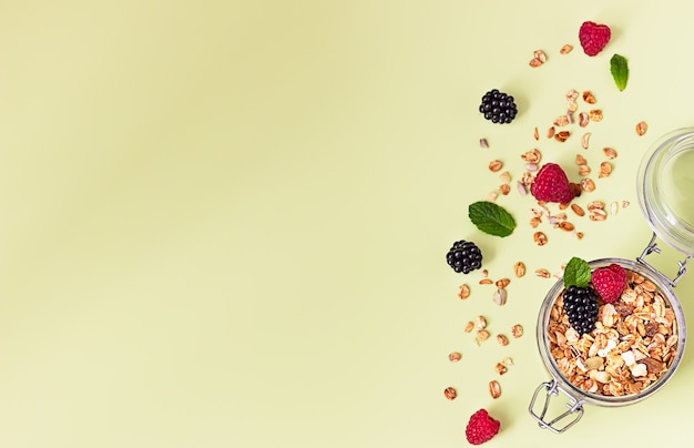Flat lay composition with muesli or granola in jar with raspberries, blackberries and mint. healthy food concept.