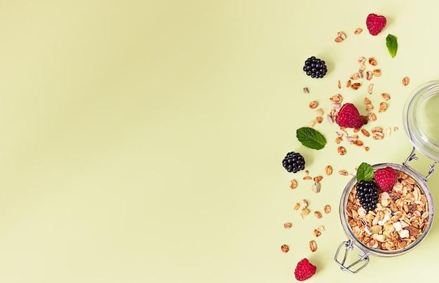 Плоская композиция с мюсли или мюсли в банке с малиной, ежевикой и мятой. концепция здорового питания.
