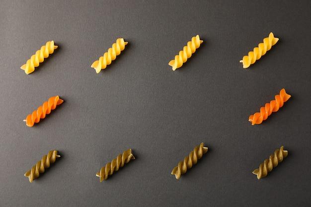 Плоская композиция с разноцветными макаронами на черном фоне, место для текста