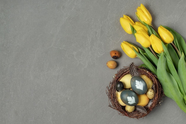 Плоская композиция с натурально окрашенными пасхальными яйцами в гнезде и желтыми тюльпанами