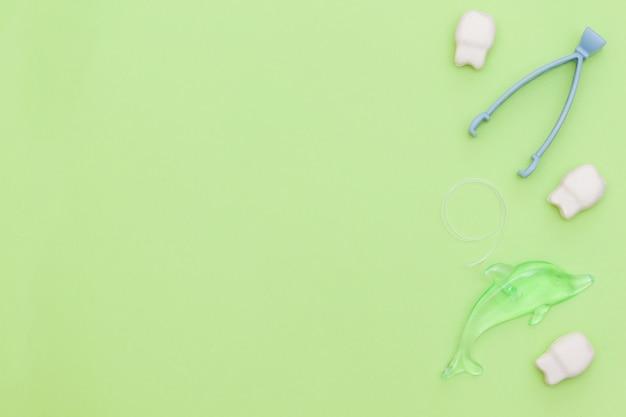 緑の背景に口腔ケア製品とフラットレイアウト構成。歯科医療と健康な歯のコンセプト。コピースペース。