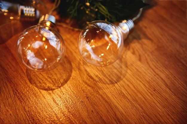Плоская композиция с орнаментом из прозрачных ламп на сосновой ветке, лежащей на деревянной доске. деревянный фон