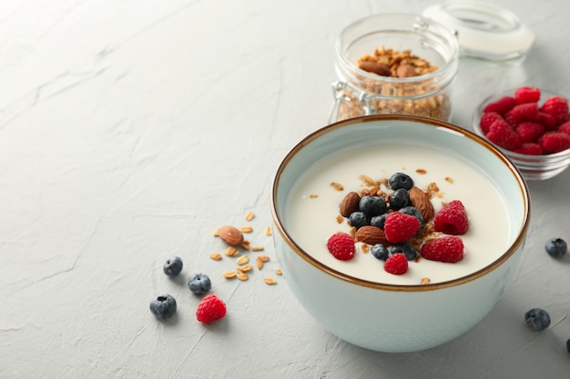 Flat lay composition with parfaits dessert and ingredients on white cement background