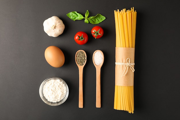 Flat lay composition with pasta ingredients on black background, space for text