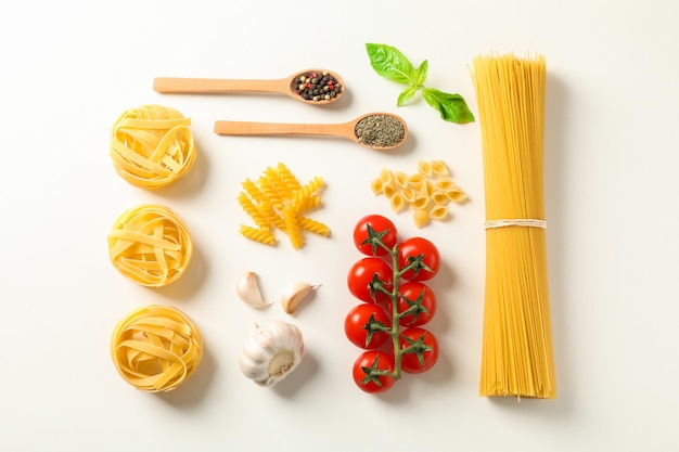 Flat lay composition with pasta ingredients on white background, space for text