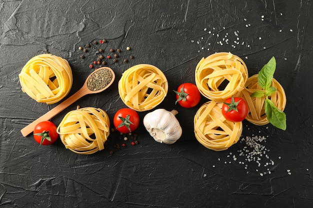 Flat lay composition with pasta, tomatoes, salt, garlic and spices on black background, space for text