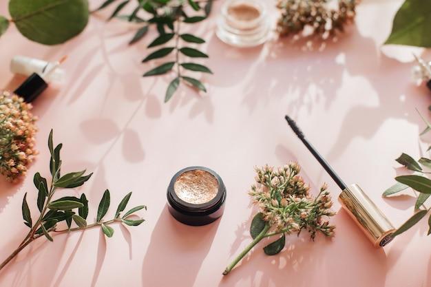Плоская композиция с продуктами для декоративного макияжа на розовом столе.