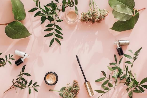 분홍색 벽에 장식 메이크업 제품으로 평평한 평신도 구성. 마스카라, 아이 섀도우, 아이 라이너 및 분홍색 테이블에 꽃과 녹색 잎.