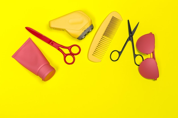 Flat lay composition with professional hairdresser tools on yellow background