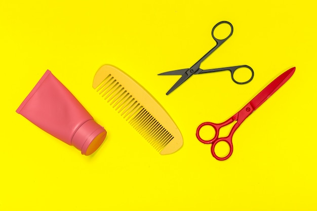 Flat lay composition with professional hairdresser tools on yellowbackground