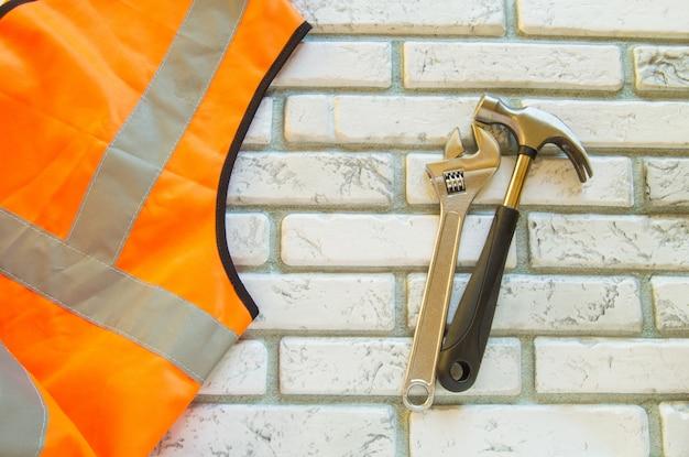 保護建設ベストとレンガ壁の背景に作業工具フラットレイアウト組成