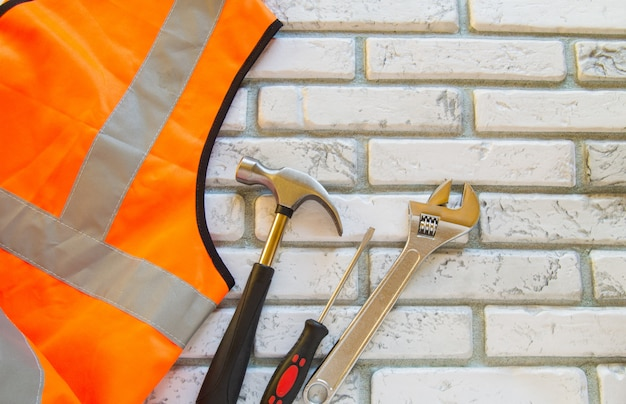 Flat lay composition with protective construction vest and working tool on brick wall background