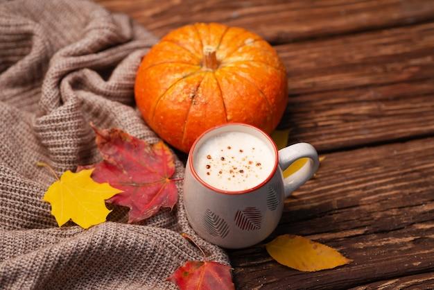 Плоская композиция с тыквой и чашкой теплого напитка