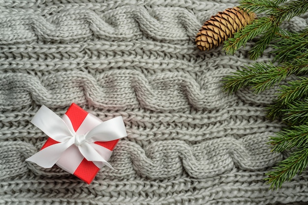 Flat lay composition with a red box, spruce branches and a pine cone on a knitted blanket. christmas gift in a red jewelry box.