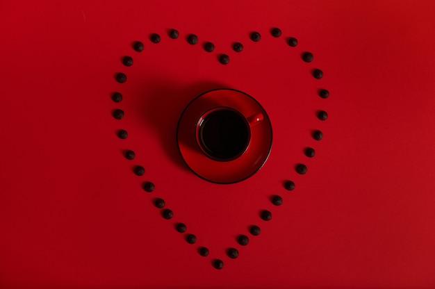 赤い表面にマルチカラーのチョコレートの丸薬が並ぶハート型の受け皿にコーヒーと赤いカップを入れたフラットレイコンポジション。コーヒーとチョコレートのコンセプト