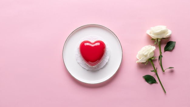 Flat lay composition with red heart cake and delicate white rose. love or valentines day concept. pink background. banner. copy space