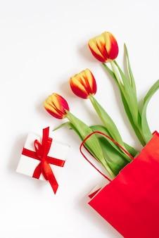 白い背景の上の贈り物と赤い紙袋に赤黄色のチューリップとフラットレイ構成。バレンタインデー、誕生日、母の日