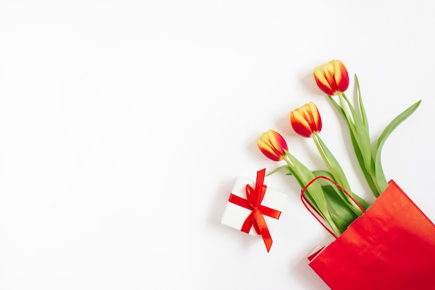 Flat lay composition with red yellow tulips in a red paper bag with gift on a white background with copy space.