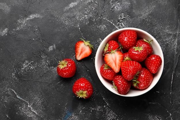 검은 배경에 잘 익은 빨간 딸기가 있는 평평한 구성
