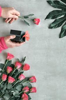 フラット横たわっていた、バラの花、ピンクのスカーフ、エキゾチックな葉の組成。心で花とギフトボックスを保持手。上面図。